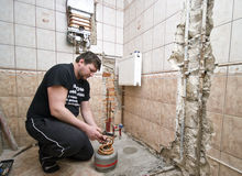 Plumber. A plumber at work with a gas torch container. Working in a bathroom, tiled walls Royalty Free Stock Image