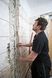 Plumber. A plumber at work with a new pipe ready to be installed. Working in a bathroom, tiled walls Stock Photography