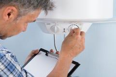 Plumber adjusting temperature of electric boiler. Plumber Holding Clipboard Adjusting Temperature Of Electric Boiler stock image