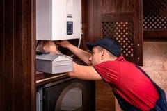 Plumber adjusts gas boiler before operating royalty free stock image