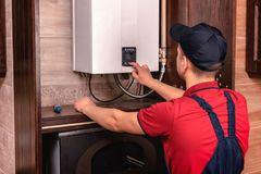 Plumber adjusts gas boiler before operating royalty free stock photo