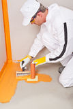 Plumber applied waterproofing. Cuff brush on the floor of the bat Royalty Free Stock Photos