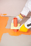 Plumber applied waterproofing. Plumber builder with brush applied waterproofing around siphon on the floor of the bathroom Royalty Free Stock Photography