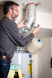 Plumber applies tape on duct work. Master plumber works on a hot water heater duct stock image
