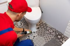 Plumber applying silicone sealant around water closet. In bathroom stock photo