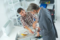 Plumber and apprentice fixing radiator with wrench. Fixing royalty free stock images