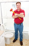 Plumber in Bathroom. Plumber or homeowner holding a plunger and standing in a modern bathroom Stock Images