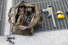Plumber workman`s bag of tools outside on a city sideway with st stock photography