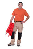 Plumber carrying hose Stock Image