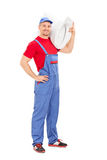 Plumber carrying a toilet bowl. Full length portrait of a plumber carrying a toilet bowl isolated on white background Stock Photos