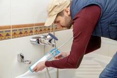 Plumber caulking bathtub. Plumber caulking bathtub with silicone glue using caulking gun Royalty Free Stock Photos