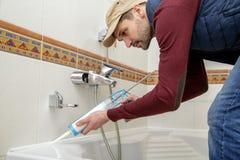 Plumber caulking bathtub. Plumber caulking bathtub with silicone glue using caulking gun Royalty Free Stock Image