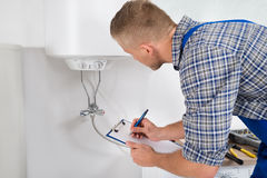 Plumber With Clipboard In Front Of Electric Boiler. Male Plumber Writing On Clipboard In Front Of Electric Boiler In Kitchen Room Stock Images