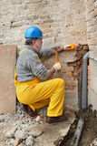 Plumber at construction site installing sewerage tube Royalty Free Stock Images