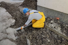 Plumber at construction site repair sewerage tube Royalty Free Stock Images