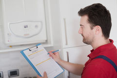 Plumber  control check on the home water boiler Stock Image