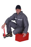 Plumber crouching. By his tool box Stock Photos