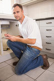 Plumber crouching and taking notes Royalty Free Stock Photos