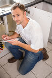 Plumber crouching and taking notes Stock Photos