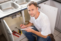 Plumber crouching and taking notes Royalty Free Stock Image