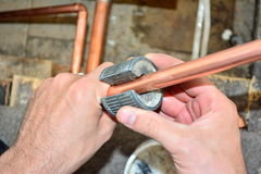 Plumber cutting copper pipe. A plumber cutting copper wipe with pipe cutter royalty free stock photo