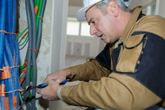 Plumber cutting pipes indoors construction. Plumber cutting some pipes indoors construction Royalty Free Stock Image
