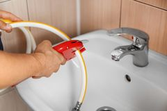 Plumber cutting water flexible hose. In bathroom close up Stock Photo