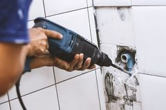 Plumber Drilling Water Pipe In Toilet Stock Image