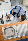 Plumber examining kitchen sink Stock Images