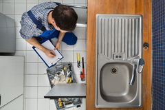 Plumber examining kitchen sink Royalty Free Stock Photography