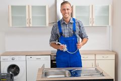 Plumber With Faucet In Kitchen Room Stock Photo