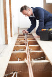 Plumber Fitting Central Heating System In House. Plumber Fits Central Heating System In House stock photo