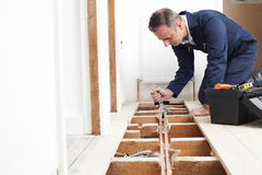 Plumber Fitting Central Heating System In House. Plumber Fits Central Heating System In House stock photography
