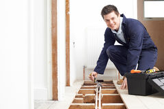 Plumber Fitting Central Heating System In House. Plumber Fits Central Heating System In House royalty free stock photo
