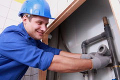 Plumber fitting water pipes. Young plumber fitting water pipes Royalty Free Stock Photography