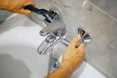 Plumber fixing bath faucet with an adjustable wrench stock photos