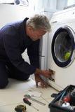 Plumber Fixing Domestic Washing Machine Royalty Free Stock Image