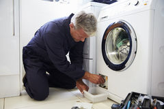 Plumber Fixing Domestic Washing Machine Royalty Free Stock Photo