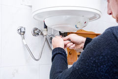 Plumber fixing electric water heater. In home stock photography