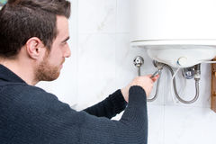 Plumber fixing electric water heater. In home stock photo