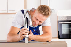Plumber Fixing Faucet In Kitchen. Happy Young Male Plumber Fixing Faucet In Kitchen stock photos