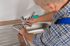 Plumber Fixing Faucet In Kitchen Sink. Male Plumber Fixing Faucet In Kitchen Sink At Home stock photos