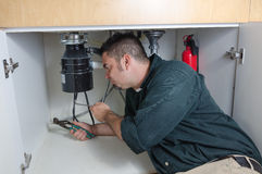 Plumber fixing a garbage disposal Royalty Free Stock Photography
