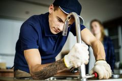 Plumber fixing kitchen sink at home Stock Images