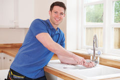 Plumber Fixing Kitchen Tap With Adjustable Wrench Royalty Free Stock Images