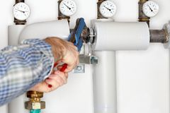 Plumber is fixing a pipe. In heating room Stock Images