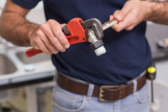 Plumber fixing pipe with wrench Royalty Free Stock Image