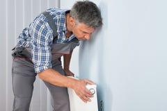 Plumber fixing radiator Stock Photos
