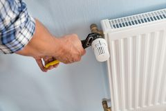 Plumber fixing radiator with wrench. Close-up Of Male Plumber Fixing Radiator With Wrench Royalty Free Stock Photography