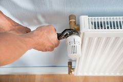 Plumber fixing radiator with wrench Royalty Free Stock Photography